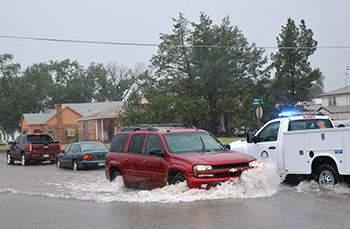 Cars drive down a flooded roadway