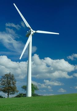 A wind turbine on a field of green grass