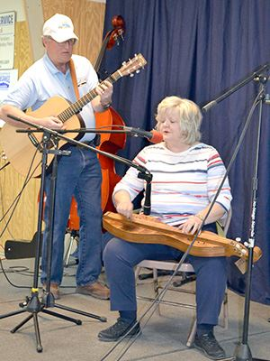 A man and a woman perform with musical instruments